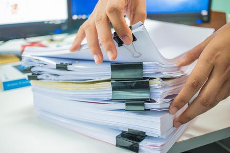 Onderneemsterhanden die aan Stapels documentendossiers werken voor financiën in bureau. Zakelijke rapporten of stapels onafgemaakt document worden behaald met zwart clippapier. Concept van zakelijk jaarverslag