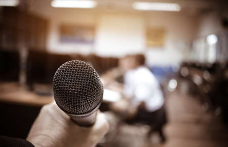 Microphones in seminar room, talking speech in conference hall light with microphone and keynote. Speech is vocalized form of communication humans, Blurred of audience in meeting room, vintage tone Stok Fotoğraf - 92942534