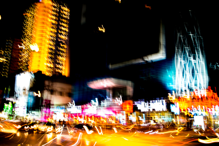 Abstract of multicolored city lights beams in motion, Moving colorful lines or light painting LED building abstraction on busy city Light trails, Rainbow and chaos black background. Vertical desigh