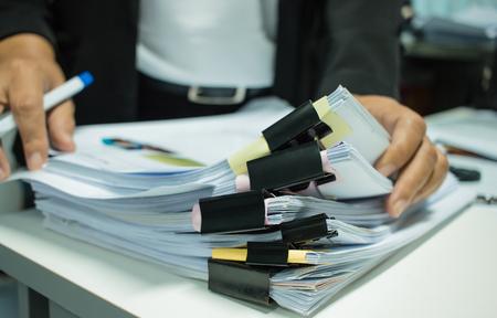 Onderneemsterhanden die aan Stapels documentendossiers werken voor financiën in bureau. Zakelijke rapporten of stapels onafgemaakt document worden behaald met zwart clippapier. Concept van zakelijk jaarverslag Stockfoto - 93051268
