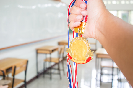 Students hands raised holding two gold medals with Thai ribbon against blur empty classroom at school greenboard background, Show success in studying, Winners success awards in educational concept.