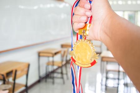De opgeheven studentenhanden die twee gouden medailles met Thais lint houden tegen onduidelijk beeld leeg klaslokaal op school greenboard achtergrond, tonen succes in het bestuderen, de successawards van Winnaars in onderwijskundig concept. Stockfoto