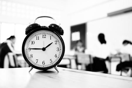 Alam-klok op houten leraarslijst wordt gevestigd in definitieve examenruimte van secundaire school, studenten van het universiteits de universitaire klaslokaal in Azië, Thailand dat. Het toont een timeoutteken. in de middelbare school, onderwijsconcept