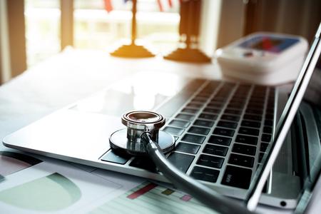 Focus Stethoscoop Dokter tafel op een laptop computer met rapport-analyse en geld over de kosten van de gezondheidszorg en vergoedingen in medische hostpital kantoor. Gezondheidszorgbegroting en bedrijfsconcept