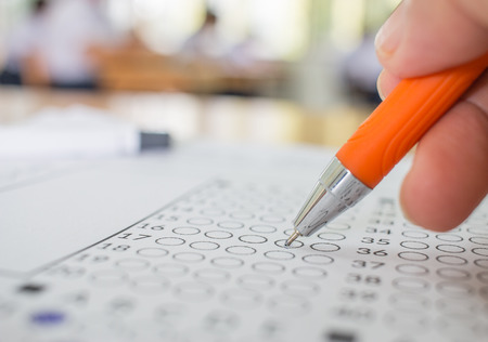 Students hand testing doing examination with pen drawing selected choice on answer sheets in school exams, blur pupils college backgroud. Education system tests concept. Stock Photo