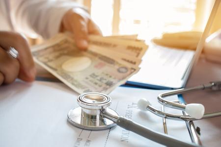 Geneeskundedokter die JPY-geld houdt voor kosten in de gezondheidszorg en vergoedingen in een medisch hoofdkantoor. Focusstethoscoop is een akoestisch apparaat voor auscultatie, waarbij interne geluiden worden beluisterd. Gezondheidszorg budget concept Stockfoto - 92848337
