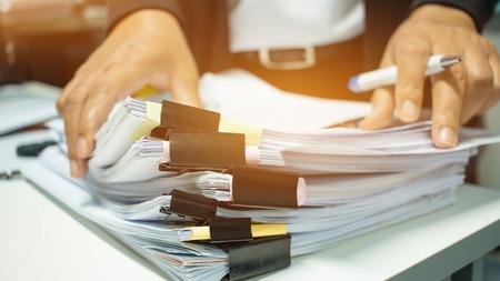 Onderneemsterhanden die aan Stapels documentendossiers werken voor financiën in bureau. Zakelijke rapporten of stapels onafgemaakt document worden behaald met zwart clippapier. Concept van zakelijk jaarverslag Stockfoto - 92931323