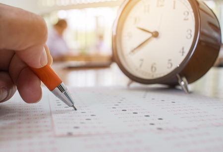 Students taking optical form of standardized exams near Alarm clock with hands holding orange pen for final examination in school, college university classroom, Education concept Stockfoto