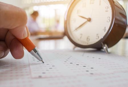Studenten die optische vorm van gestandaardiseerde examens dichtbij wekker nemen met handen die oranje pen voor recent examen in school, universiteits universitair klaslokaal, Onderwijsconcept houden