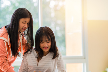Asian University or college students studying together with tablet,laptop and documents paper for report near windows in classroom. Happy Asian young woman doing group study in Education class Concept