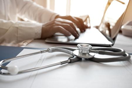 Doctor's bezig met laptopcomputer, schrijven recept klembord met records record papier mappen op Bureau in het ziekenhuis of kliniek, gezondheidszorg en medische concept. Focus op stethoscoop Stockfoto - 92931328