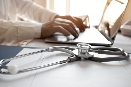 Doctor's working on laptop computer, writing prescription clipboard with record information paper folders on desk in hospital or clinic, Healthcare and medical concept. Focus on stethoscope Stockfoto