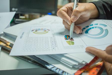 Zakenman die rapportendocumenten met grafieken, grafieken op Stapels documentendossiers voorbereiden voor financiën in bureau. Stapels onafgemaakt document worden behaald met paperclip. Concept van zakelijk jaarverslag. Stockfoto - 93014749