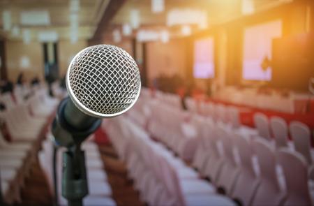 De microfoons op samenvatting vaag van toespraak in seminarieruimte of de voor sprekende conferentiezaal steken, witte stoelen voor mensen in de vergaderingszaal van de gebeurtenisvergadering in hotel uit. Stockfoto - 92931331