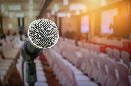 Microphones on abstract blurred of speech in seminar room or front speaking conference hall light, white chairs for people in event meeting convention hall in hotel. Imagens - 92931331