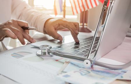 Arts die aan laptop computer met rapportanalyse en geld over Gezondheidszorgkosten en prijzen in medisch hoofdkantoor werkt. Focus stethoscoop op tafel. Gezondheidszorgbegroting en bedrijfsconcept Stockfoto - 92931332