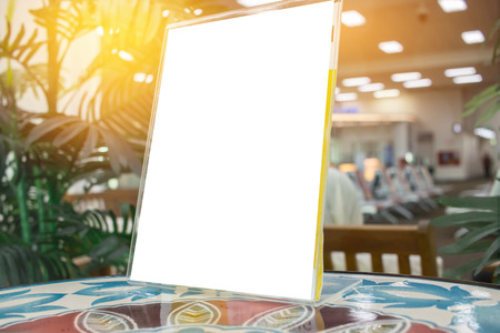 Mock up white Label for blank menu frame in Bar restaurant cafe., Stand for booklets with  sheets paper tent card on table cafeteria, blurred background insert for text of customer. Space for texting.