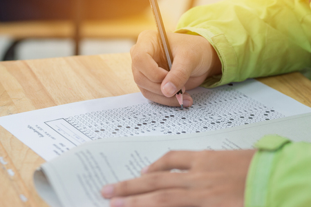 high school or university student hands taking exams, writing examination on paper answer sheet optical form of standardized test on desk doing final exam in classroom. Education  literacy concept.