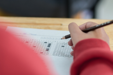 Schoolstudentenhanden die examens nemen, onderzoeksruimte schrijven met holdingspotlood op optische vorm van gestandaardiseerde test met antwoorden en Engels document blad op bureau die definitieve examen in klaslokaal doen. Stockfoto - 99362998