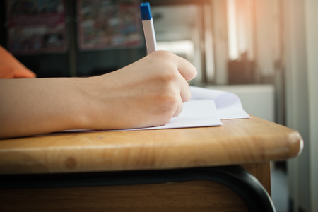 Hands with pencil over application form, Students taking exams, writing examination room with undergraduate students inside. Student sitting learning lessons doing final exam in classroom. Stockfoto