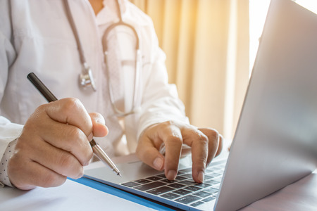 Doctor's writing and working on laptop computer, writing prescription clipboard with record information paper folders on desk in hospital or clinic, Healthcare and medical concept.