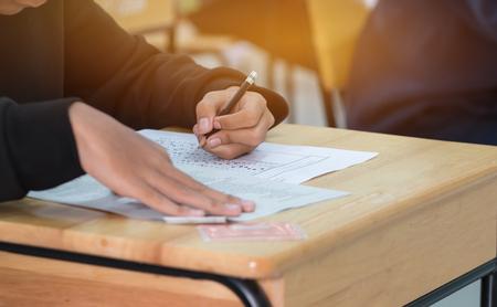 liceum lub uczelnia ręce zdające egzaminy, egzamin pisemny na kartce odpowiedzi optyczna forma standaryzowanego testu na biurku podczas egzaminu końcowego w klasie. Koncepcja edukacji umiejętności.