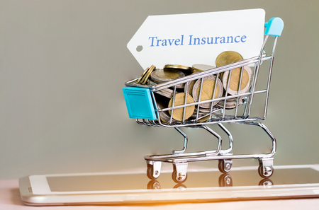 Many coins and tag Travel insurance in small shopping cart on tablet. Concepts online shopping consumers can buy insurance directly from anywhere, home or office. Taking few clicks via Internet web. Stockfoto - 99365007