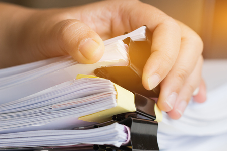 Businessman hands searching unfinished documents stacks of paper files on office desk for report papers, piles of papers sheet achieves with clips on desks, Document is written, drawn,presented. Stockfoto