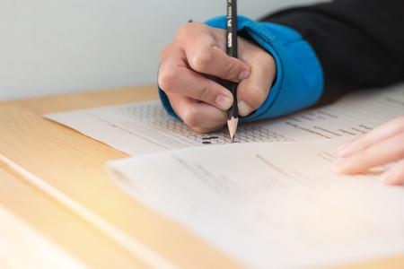 lycéen ou étudiant universitaire mains prenant des examens, examen écrit sur une feuille de réponse papier sous forme optique de test standardisé sur le bureau faisant l'examen final en classe. Concept d'alphabétisation de l'éducation.
