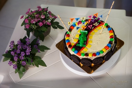 Delicious vanilla cake for children birthday party decorated with toys sport cars and chocolate cookies photo