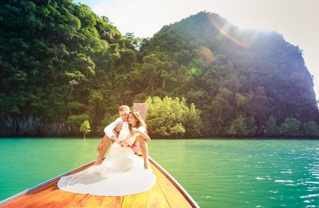 longtail: handsome groom hugging his brunette bride in white wedding dress sitting on longtail boat in thai island lagoon