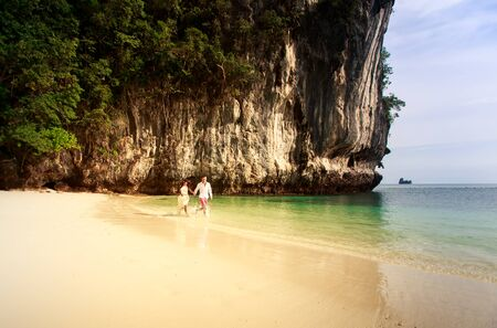 handsome groom run with his beautiful brunette bride in long white wedding dress on island bay with green mountain background in Thailand photo
