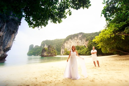 barefoot blonde: blonde bride and handsome groom stand on the sand beach barefoot near green jungle trees Stock Photo