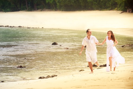 barefoot blonde: blonde bride and handsome groom run barefoot on sandy island beach against rocks and water background