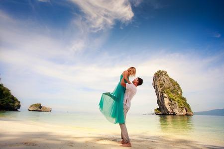 luna de miel: hombre hermoso joven se sostiene a su novia hermosa rubia de vestido azul