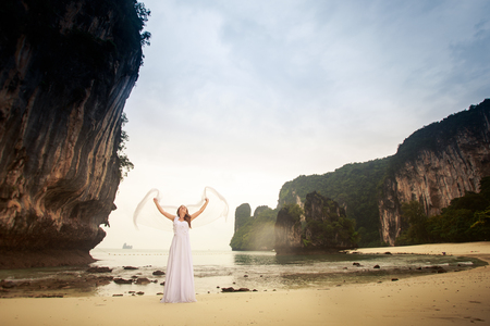 barefoot blonde: blonde bride in wedding dress dance with white veil stand barefoot on a sand beach against cliff and island sea water background