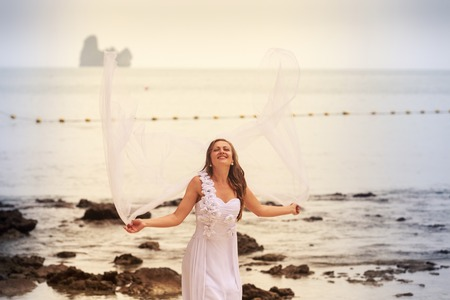 barefoot blonde: blonde bride in wedding dress jump with white veil stand barefoot on a sand beach against cliff and island sea water background Stock Photo