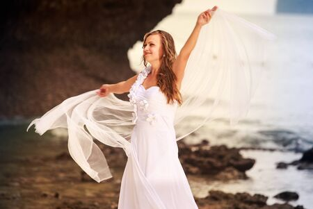 barefoot blonde: blonde bride in wedding dress whirls with white veil stand barefoot on a sand beach against cliff and island sea water background