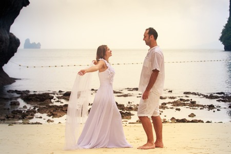 blonde bride and young groom dance barefoot with white veil standing on sandy beach against cliff and island sea water background photo
