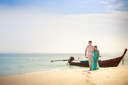 tail woman: hermosa mujer rubia en elegante vestido de paseo con su guapo marido en la playa de arena blanca cerca del mar azul con una larga cola de barco en el fondo Foto de archivo