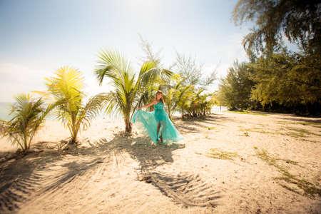 beautiful blonde woman pose in elegant dress in green palm leafs photo