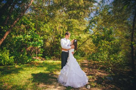 young brunette bride and handsome groom embrace in green jungle photo