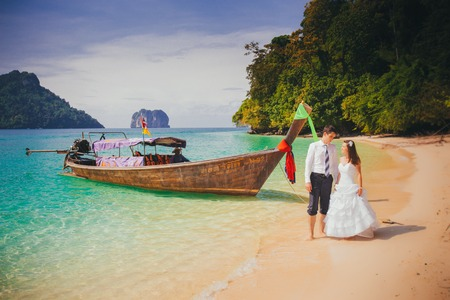 young brunette bride and groom stand near longtail boat at sand beach against azure sea and rocky island photo