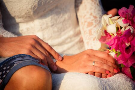 hands of bride and  groom with pink bouquet