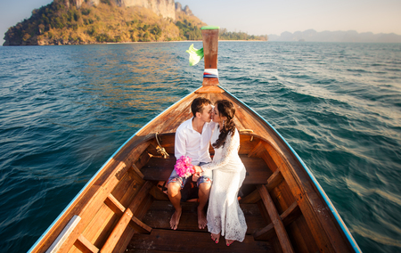 brunette bride in white wedding dress and handsome groom kiss in longtail boat drifting  to island at sunrise