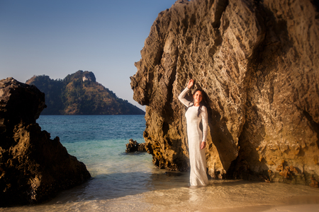 brunette bride in white wedding dress leans on large rock at sand beach against tropical islands Stock Photo