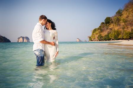 romantic hug: bride and groom hug half in transparent water against cliffs
