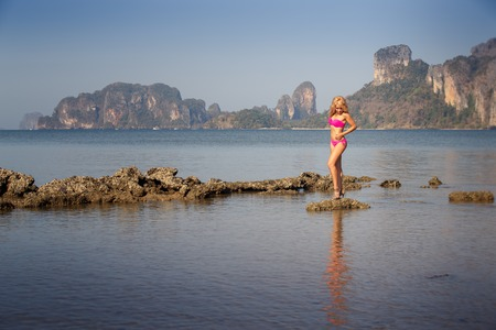 pretty blonde girl in pink swimsuit stand on stones in sea against cliffy island photo