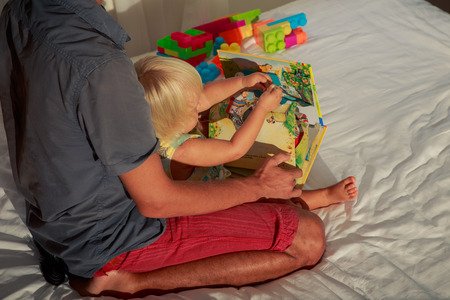 nice butt: little blonde girl and father sit backside view on sofa and look into child book with raised pictures