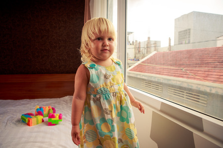 sideview: little blonde girl in colourful dress stands by window on sofa side-view